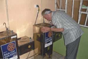 Dr. Omero Iung sampling the healthy safe drinking water